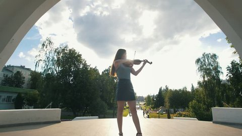 Attractive woman stands under the arch playing violin in front of park