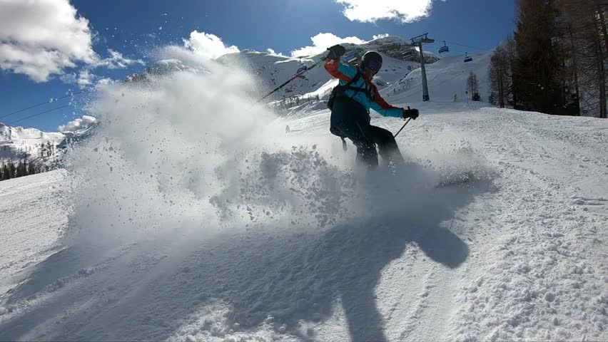 Young boy skiing. A man enjoys skiing in the Alpine resort. Skier spraying snow into the camera. Stabilized footage. Slow motion.  | Shutterstock HD Video #1013911190