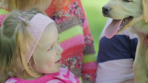 Little girl touching the puppy's nose