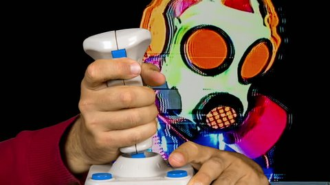 a freaky gasmask person using a retro computer arcade game joystick. this version has intentional overlayed video distortion and glitch effects