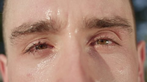 SLOW MOTION, CLOSE UP, MACRO, DOF: Unknown adult male's eyes after a tough workout in the sunny nature. Unrecognizable sweaty Caucasian man looking around park after exercising on a hot summer day.