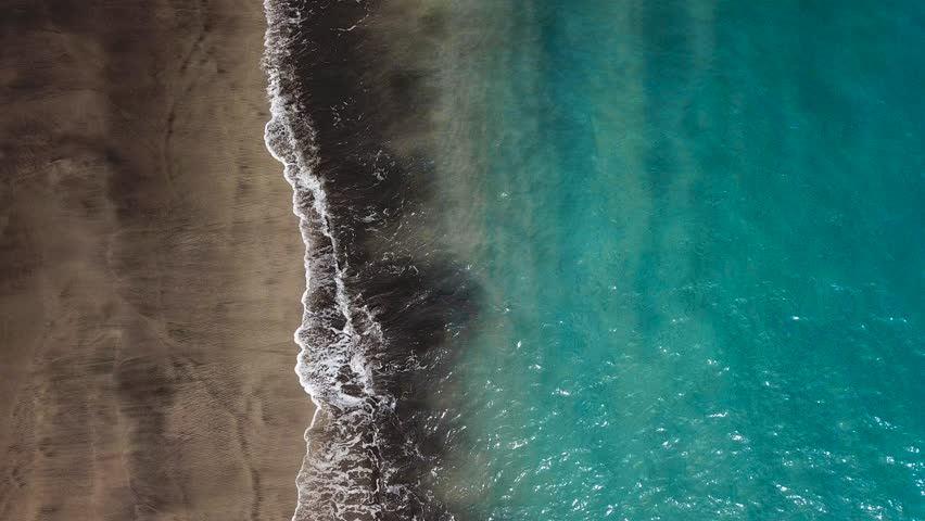 Top view of a deserted black volcanic beach. Coast of the island of Tenerife. Aerial drone footage of sea waves reaching shore