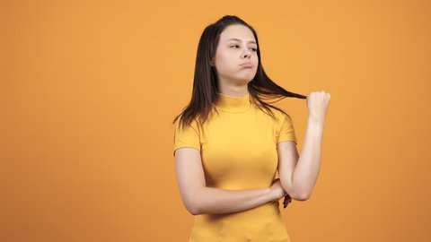 Unhappy woman on vivid orange background. Beautiful bored person. Tired and annoyed teenager
