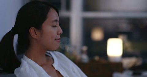 Woman taking a deep breath at home in the evening