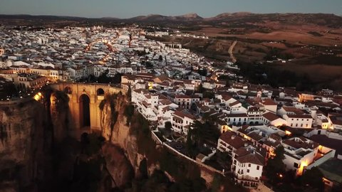 Aerial evening view of an ancient Spanish city Ronda in Andalucia. Drone flying over the famous bridge Puente Nuevo connecting the two parts of the Old Town and the huge cliff on which the city is bui