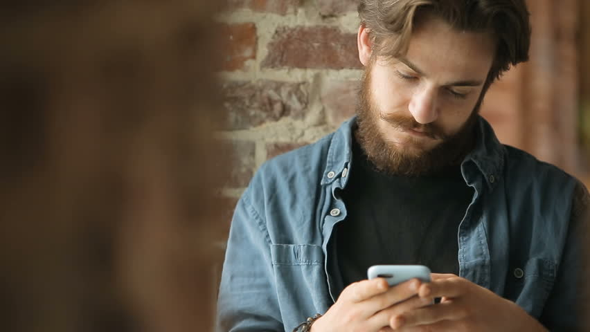 Smiling handsome man texting a message before brick wall, wearing blue smart shirt and black t-shirt, having a break with gadget | Shutterstock HD Video #1013968160