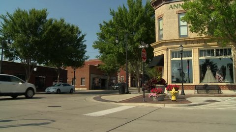 Cars drive into a small town's business district in the morning for a day of shopping.