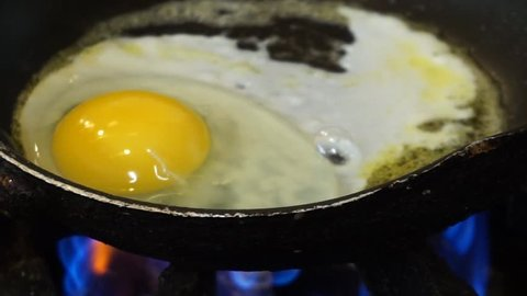 An egg white and yolk frying sunny side up in a pan on open gas flame sizzling and popping to a crisp healthy breakfast protein treat.  No carb diet friendly option for nutrition to feed the body
