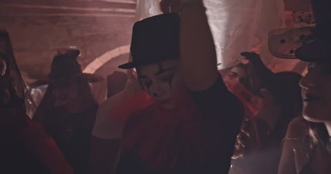Woman in evil clown costume and scary make-up dancing at Halloween nightclub party with friends