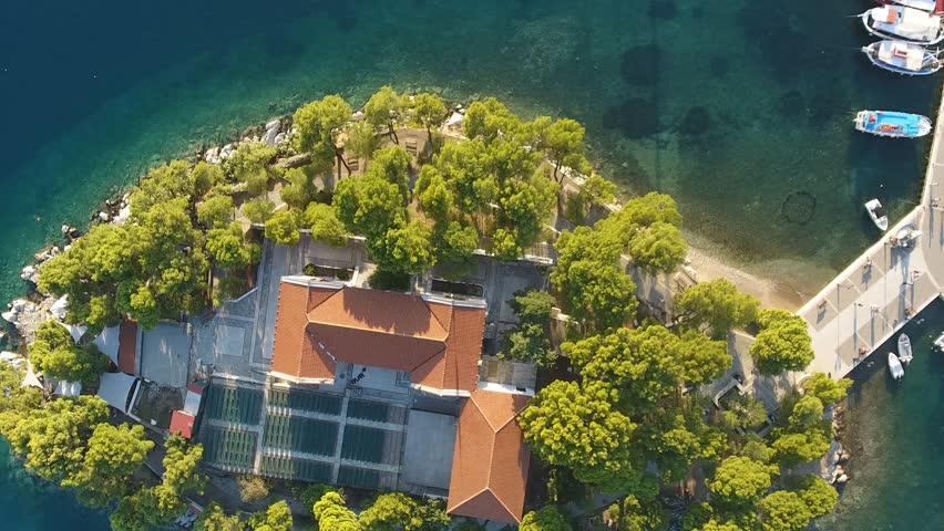 Aerial view of a small island with a house in Skiathos, Greece. Bird's eye view of a residence on an island during sunny summer day.