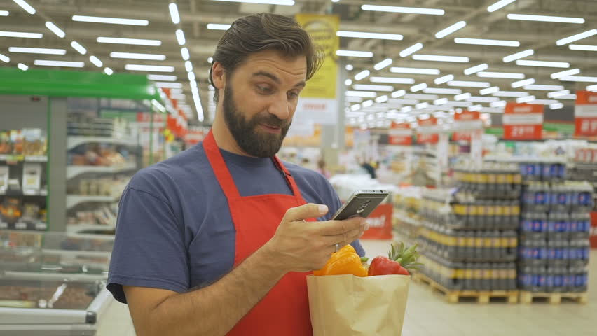 Smiling supermarket employee using mobile phone and holding shopping bag in supermarket | Shutterstock HD Video #1013987480