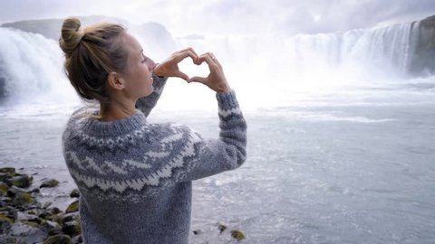 Young woman in Iceland making heart shape finger frame on spectacular waterfall loving the beauty in nature, tourism travel people concept in Northern Europe countries 4K