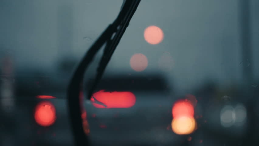Slow motion and defocused of rain drops on windshield and car wipers are removing rains. Driving on rainy highway.