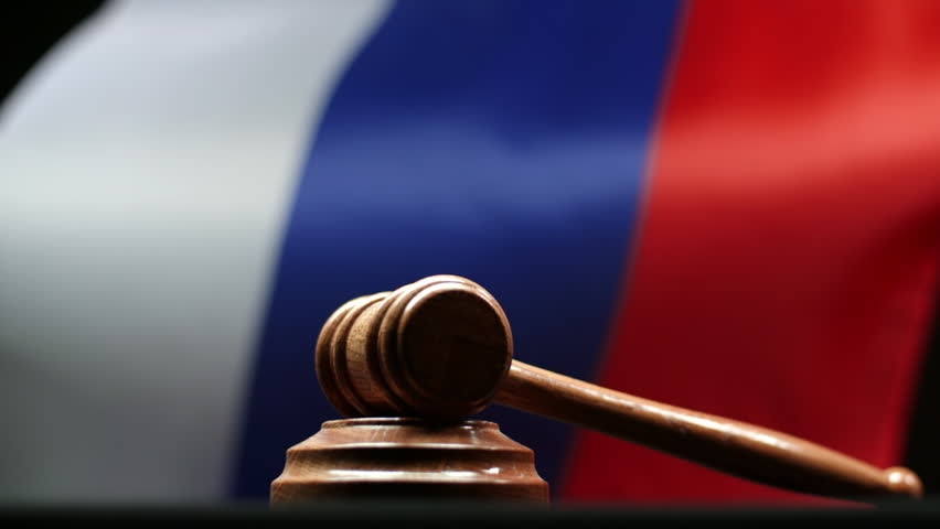 Judge's wooden gavel on block against Russian flag waving in Russian Federation court room | Shutterstock HD Video #1014022850