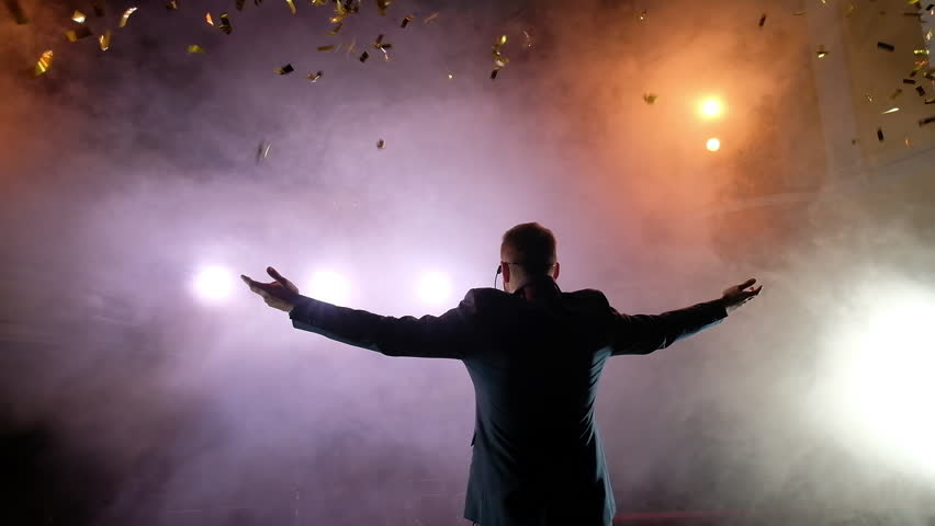Successful businessman with arms up celebrating his victory. Celebrating success. angle view of excited young men keeping arms raised and expressing positivity while stands on the stage, slow motion | Shutterstock HD Video #1014025070