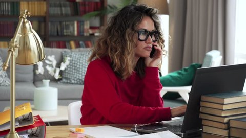 Beautiful curly woman in thirties of fair complexion in red jersey and glasses talks on mobile phone friendly while working typing on laptop in stylish room at home