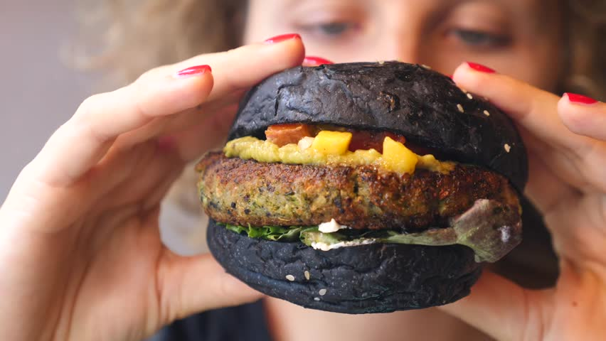 Closeup Of Woman Mouth Eating Vegan Burger. Closeup. | Shutterstock HD Video #1014055610