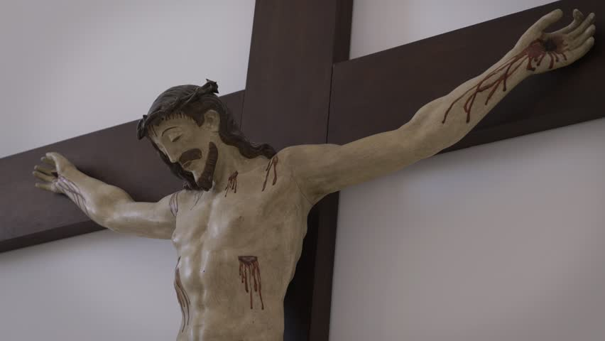 Jesus Christ Crucified In Cross. Religious sculpture of Jesus christ crucified in a cross, Tilt down.