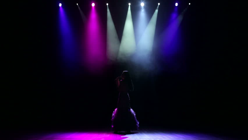 A beautiful girl vocalist performs a song on the stage lit with multi-colored searchlights. Beautiful girl sings a song on illuminated stage.