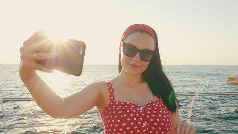 fa002d431f Pretty woman using black mobile phone by the sea beach. Girl in retro red  polka