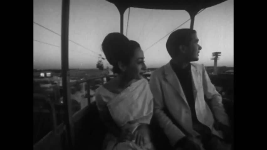 CIRCA 1960s - An Indian couple rides a sky tram at dusk at the 1964 New York World's Fair.