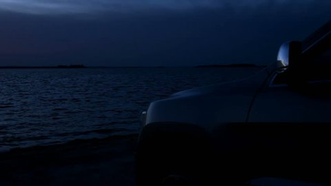 Silhouette of a SUV car at the beach with oceanview at twilight