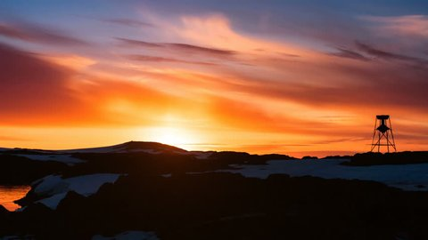 Antarctica Nature. Beautiful cloudy dramatic sky with sun rising up. Colorful orange sunset. Clouds in sky flow. Majestic winter landscape. Travel background. 4K Slow Motion Time Lapse Parallax
