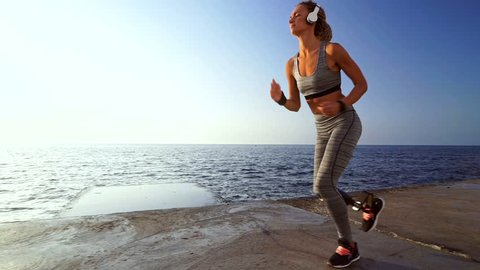 Side view of Concentrated disabled athlete woman in headphones with prosthetic leg running at the beach
