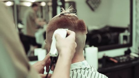 Barber cuts the hair of the client with clipper slow motion close up