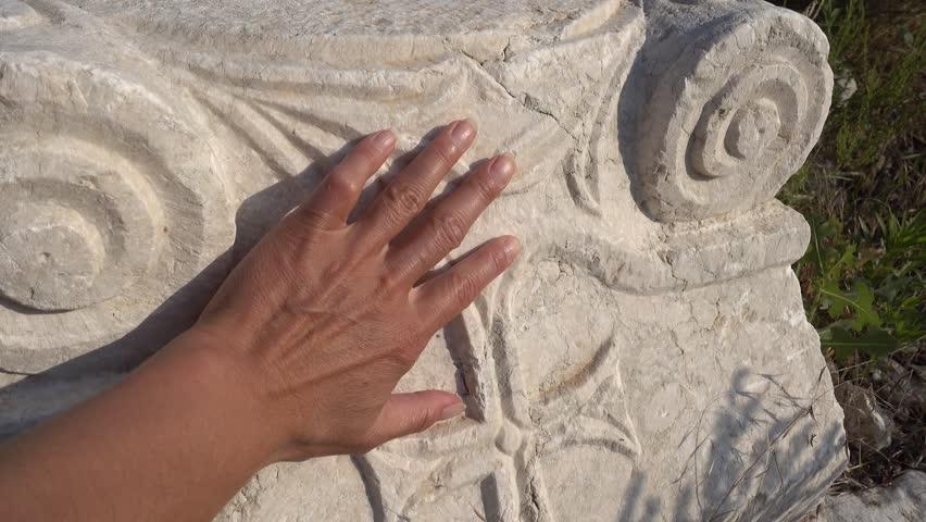 Antalya region, Turkey - 8th of July 2018: 4K Sagalassos ancient city tour - Hand touching a chrisscross engraved on the antient column basement