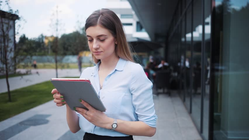 Business woman uses tablet computer stand near business center look at camera smile attractive technology girl internet young digital work screen smart student touch professional holding portrait | Shutterstock HD Video #1014212840