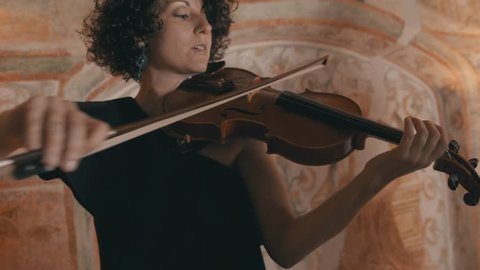 Lovely female violinist plays her violin quickly during a crescendo
