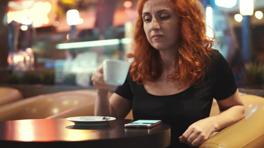 Young woman scrolls tape in social networks on the smartphone in the evening sits at table in chair in cafe by the window and drinks hot coffee on a bright background of the bokeh  | Shutterstock HD Video #1014230030