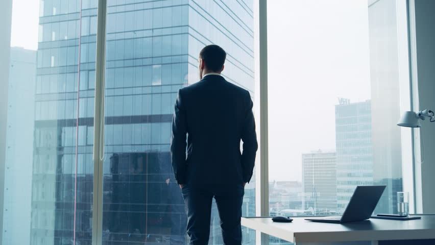 Back View of the Thoughtful Businessman wearing a Suit Standing in His Office, Hands in Pockets and Contemplating Next Big Business Deal, Looking out of the Window.