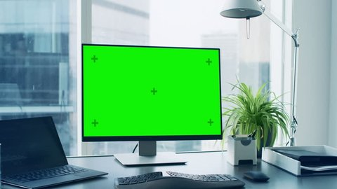 Close-up Shot of the Office Desk with Green Mock-up Screen Personal Computer Standing on it. Modern Stylish Room with a Big City Business District View.