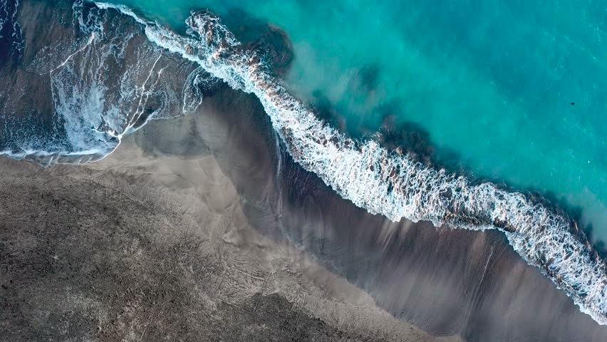 Top view of a deserted black volcanic beach. Coast of the island of Tenerife. Aerial drone footage of sea waves reaching shore | Shutterstock HD Video #1014239090