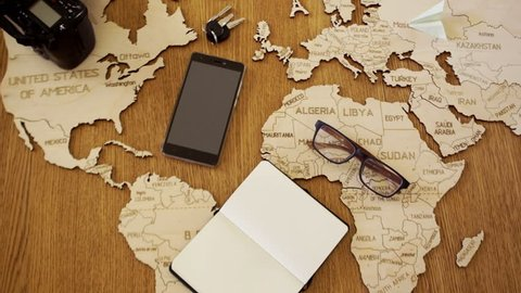 A world map made of wood. A man writes a plan of his travels in a notebook. Preparation for travel. Travel agency