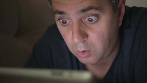 A man in a blue T-shirt in a dark room lying on the couch watching an electronic tablet. Fear and surprise on the face.