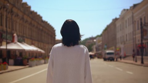 backview of a woman walking in old part of town.lady passes cafes and restaurants on the sidewalk.
