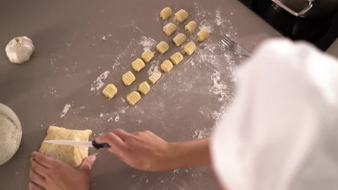 4K cooking footage, close up female cook preparing dough for fresh gnocchi in kitchen top view