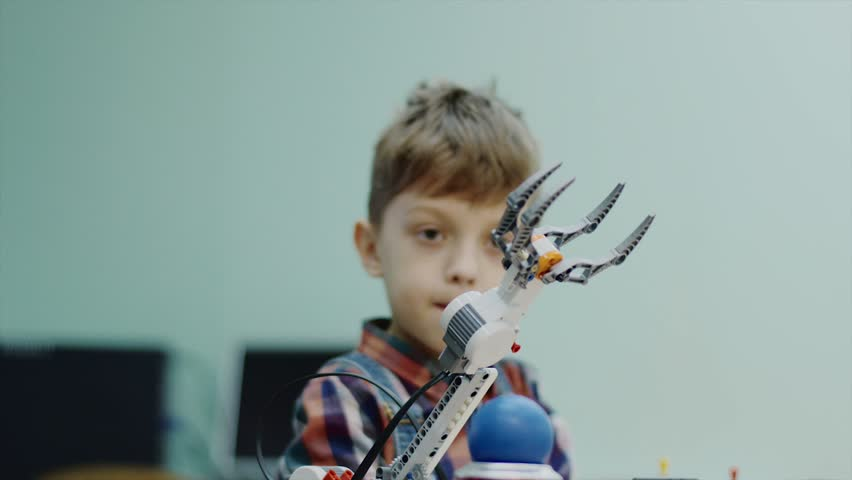 Little child boy is playing with robotic arm in a room. He is controlling it and taking ball by gadget, smiling and rejoicing | Shutterstock HD Video #1014274910