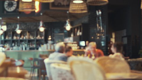 Blurred image of the interior of a large beautiful restaurant with bright lighting. A happy family is sitting at a restaurant at a table, having dinner, talking. Defocussed interior