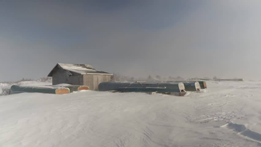 Grounded freighter canoes and boathouse in windy winter snow, northern Quebec on James Bay