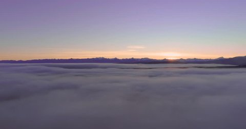 Aerial shot over a sea of clouds during sunset with snowcapped mountains in New Zealand