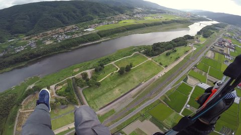 Solo Paralgider does a spiral dive and landing at a park in Japan in Summer