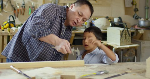 Handheld shot with tilt down of Asian father in plaid shirt showing caliper to little boy and helping him measure wood plank while working together in carpentry workshop