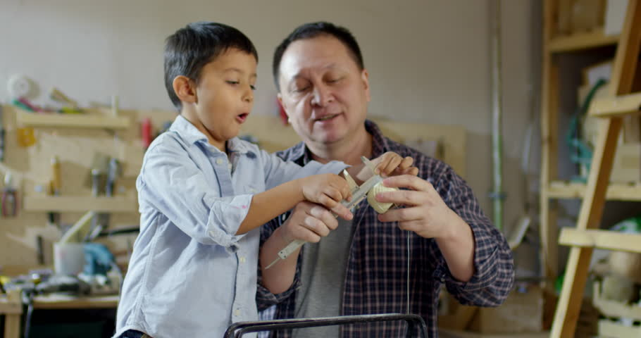 Medium shot of Asian father talking to his little son and explaining how to use caliper while spending time with him in workshop. Curious boy trying to measure handles of tool box