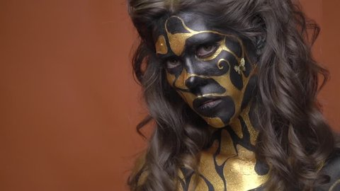 Brunette with a lush hairdo in black and gold body art posing on a brown background