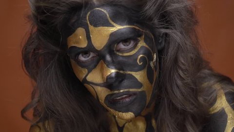 Brunette in black gold makeup touches her face