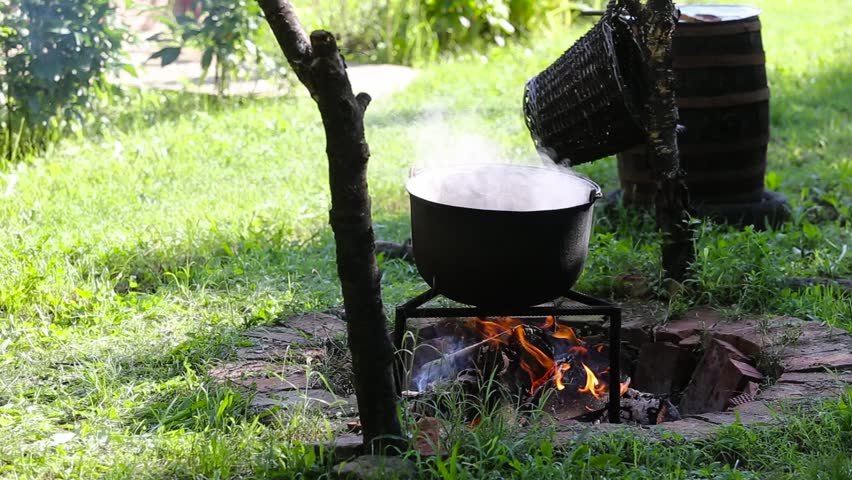 Iron cast cauldron boiling a stew over open log fire in the backyard of a rural house